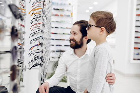 Father with little son in the glasses store