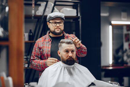 Uomo alla moda seduto in un negozio di barbiere Archivio Fotografico