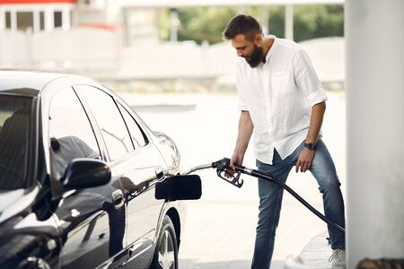 ハンサムな男は車のタンクにガソリンを注ぎます