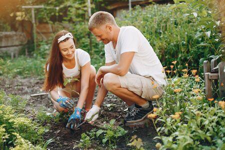 Hermosa pareja trabaja en un jardín cerca de la casa