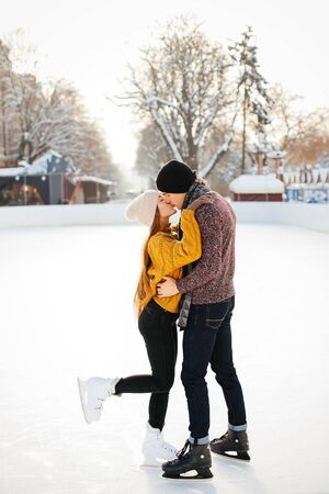 Beautiful couple have fun in a ice arena. Elegant girl in a yellow sweater.