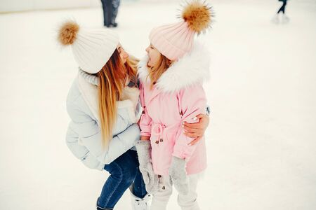 Family in a winter park. Mother with daughter in a ice arena Banco de Imagens