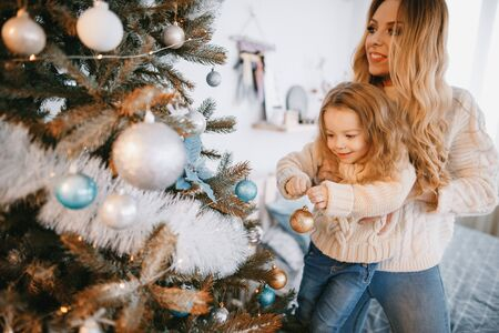 mother and daughter decorating the tree Фото со стока