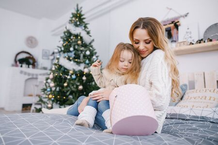 mother and beautiful blonde baby girl opening gifts Stock Photo
