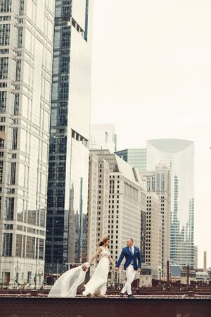 Beautiful bride in a long white dress. Handsome fiance in a blue suit. Couple in a big city