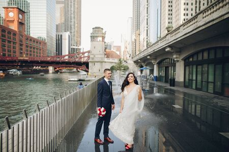 Elegant wedding couple walking in a summer city. Man in a blue suit. Woman in a white elegant dress with bouquet of roses Stock Photo