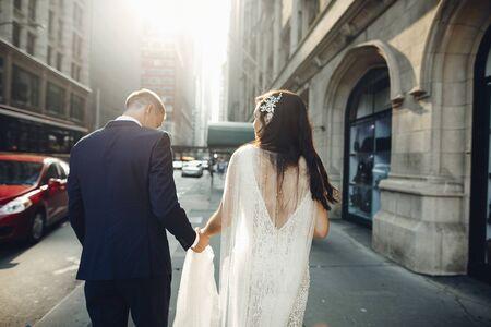 Elegant wedding couple walking in a summer city. Man in a blue suit. Woman in a white elegant dress