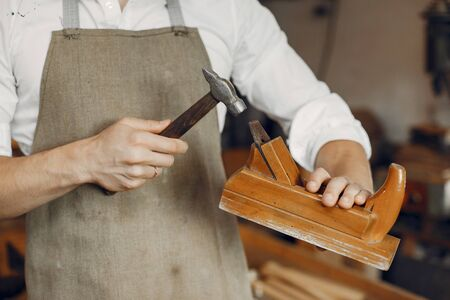 Man working with a wood. Carpenter in a white shirt. Man with a chisel and a hammer