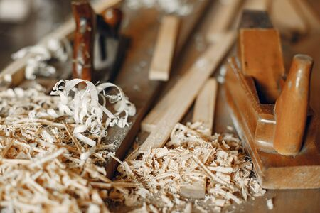 Man working with a wood. Carpenter in a white shirt. Man with a chisel