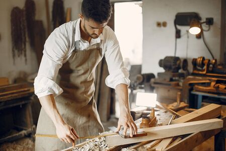 Man working with a wood. Carpenter in a white shirt. Worker measures a board