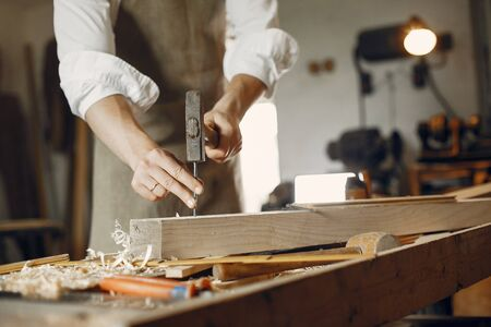 Man working with a wood. Carpenter in a white shirt. Man hammering nails into the wood