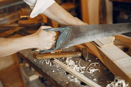 Man working with a wood. Carpenter in a white shirt. Worker with a saw Foto de archivo