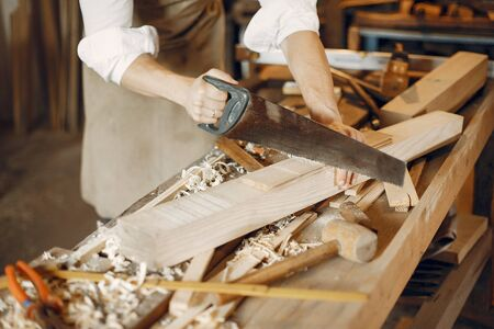 Man working with a wood. Carpenter in a white shirt. Worker with a saw