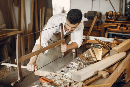Man working with a wood. Carpenter in a white shirt