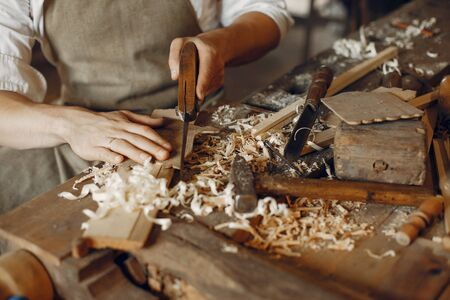Man aan het werk met een hout. Timmerman in een wit overhemd Stockfoto