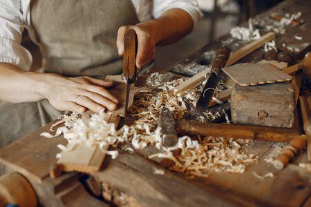 Uomo che lavora con un legno. Carpentiere in camicia bianca Archivio Fotografico