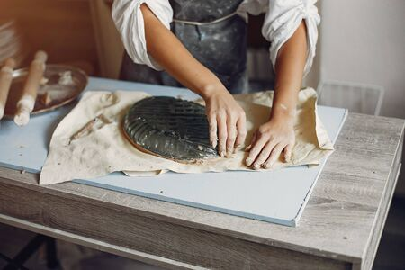 Woman in a pottery. Master make a dishes. Artist works with a clay
