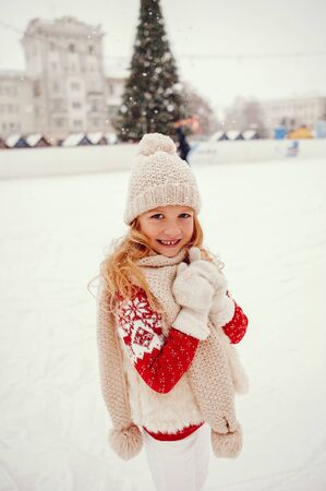 Cute and beautiful little girl in a winter city