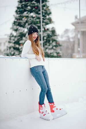 Cute and beautiful girl in a white sweater in a winter city Banco de Imagens