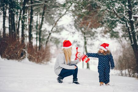 Little girl with mother playing in a winter park Stock Photo - 136742809