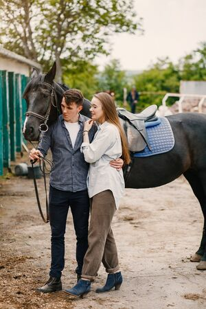 Cute loving couple with horse on ranch Stock fotó