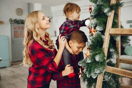 Family standing at home near christmas tree