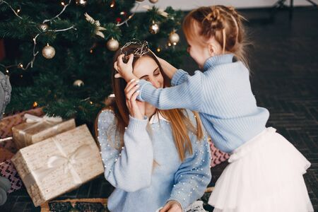 Beautiful mother in a blue sweater. Family with cristmas gifts. Little girl near christmas tree
