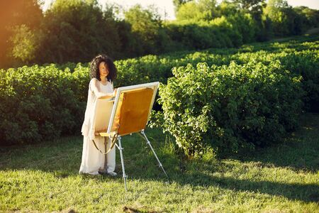 Beautiful adult woman drawing in a summer field Banco de Imagens