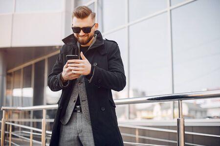 Hombre con un traje elegante. Hombre de negocios en una ciudad de verano Foto de archivo