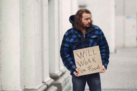 Homeless man in a durty clothes autumn city Stock Photo