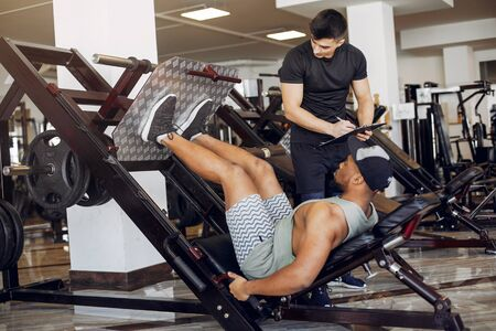 Sports men in the gym. A man performs exercises. Guy in a black t-shirt