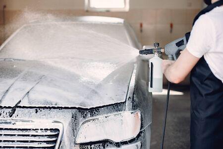 Man in a garage. Worker washing a car. Guy spray a soap Imagens