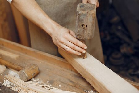 Man working with a wood. Carpenter in a white shirt Stock Photo