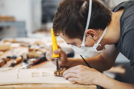 Un uomo scolpisce un albero. Il falegname lavora con il bruciatore in uno studio. Un ingegnere fornisce una forma ad albero