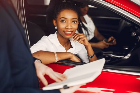 Two stylish black women in a car salon Stock Photo