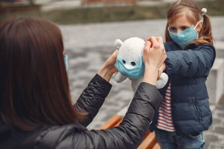 Woman in a disposable mask is teaching her child to wear a respirator Фото со стока