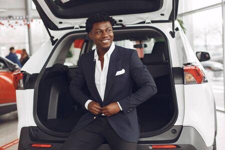 Handsome and elegant black man in a car salon
