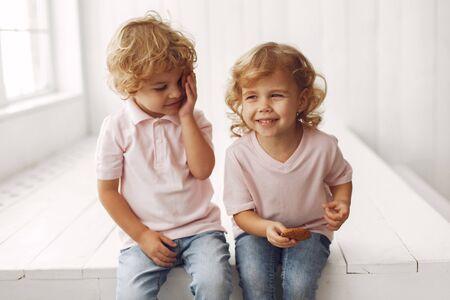 Süße Kinder, die zu Hause Kekse essen