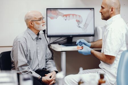 Old man sitting in the dentists office Фото со стока