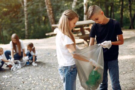 Children collects garbage in garbage bags in park Standard-Bild