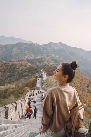 stylish girl visiting the Great Wall of China near Beijing during autumn season.
