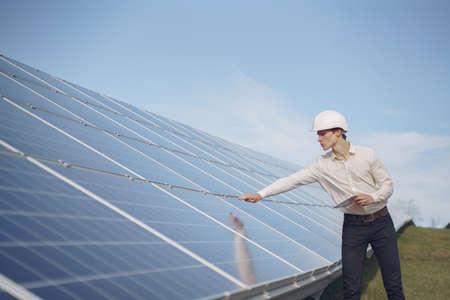 Businessman in a white helmet near solar battery