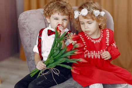 Elegant little kids in a studio with bouquet of tulip Standard-Bild