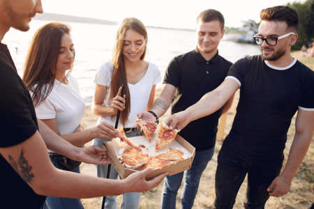 Young people eating pizza smoking hookah outside