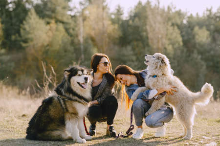 Women in a spring forest. Girls with cute dogs. Stylish friends walks.