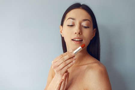 Beautiful girl standing in a studio with red lipstick Standard-Bild