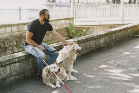 Blind man with guide dog in a summer city Stock Photo