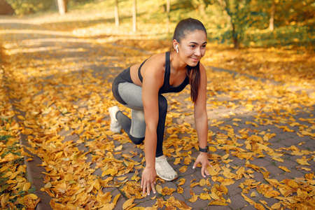 Sports girl in a black top training in a autumn park
