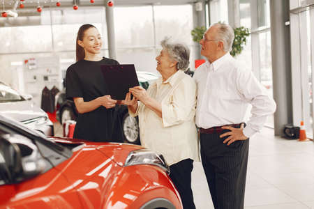 Stylish and elegant old couple in a car salon