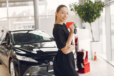 Stylish and elegant woman in a car salon